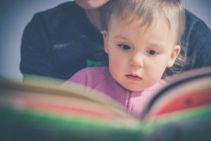Parent reading book to young child