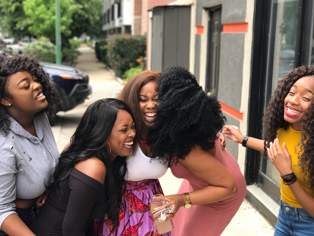 Five black women talking and laughing