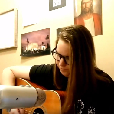 Rachel Gunderson playing a guitar and singing.