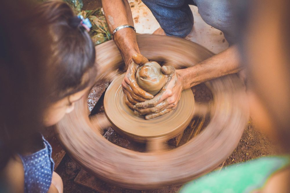 hands shaping clay on wheel as young girl watches