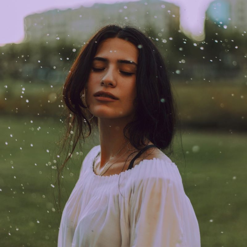 Woman in white shirt with green background under rain
