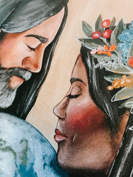 Man and woman of color wearing white clothing holding earth between them (detail of the man)