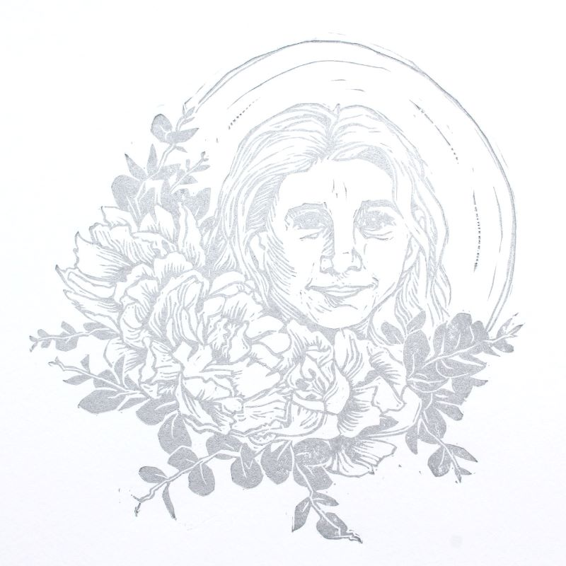Silver linoleum block print of circle with flowers surrounding smiling woman's face