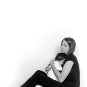 Woman sitting on floor holding dark haired baby