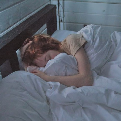 Woman sleeping in bed with white sheets and pillows