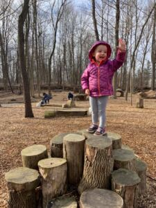 Toddler girl in pink coat standing on stump of wood and waving hand like a queen