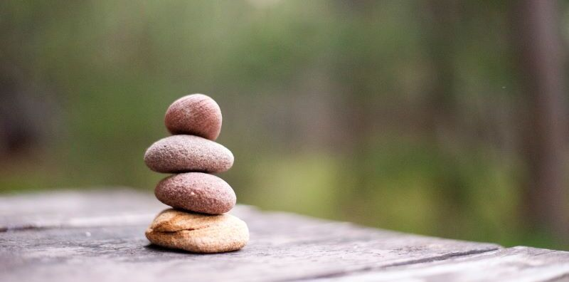 Four pebbles stacked on table outdoors