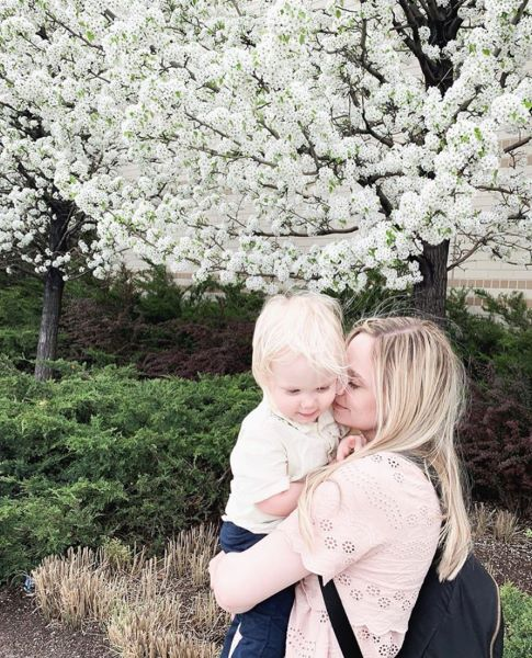 Blonde-haired woman holding toddler in front of tree with white blossoms