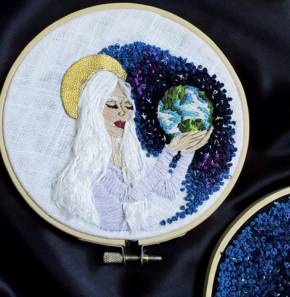 Embroidered Heavenly Mother holding earth in her hands