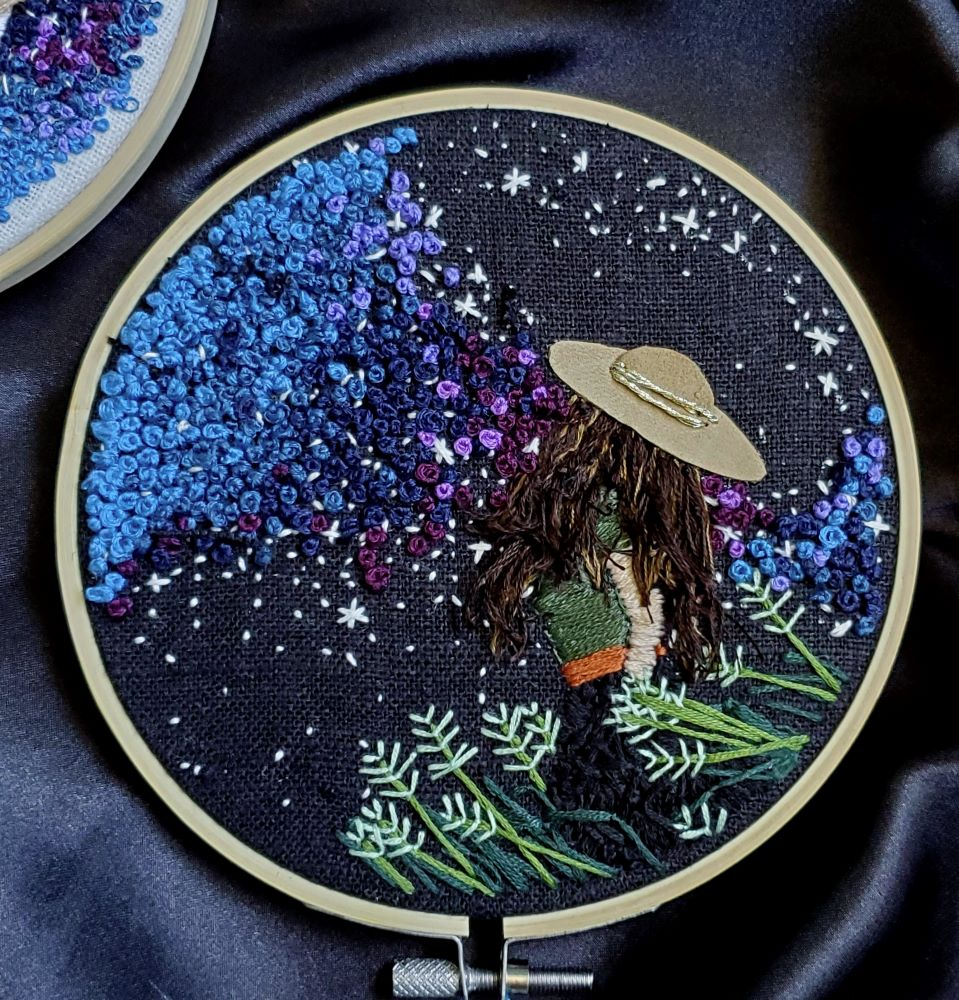 Embroidered woman looking at stars