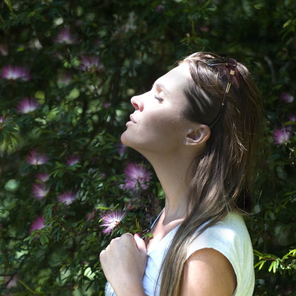 Woman with closed eyes and head tilted upwards towards the sunlight
