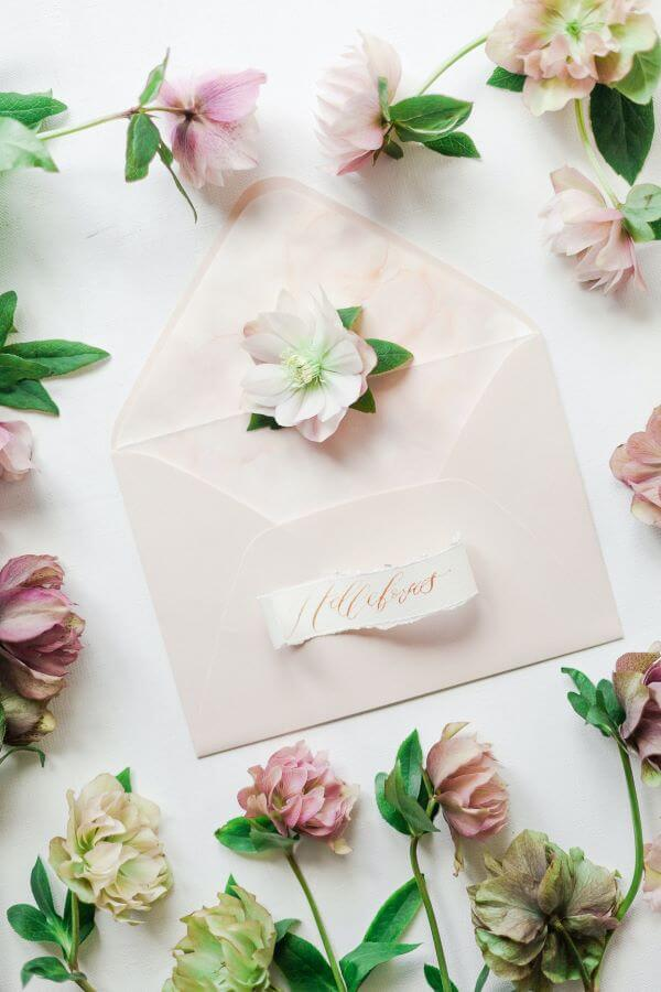 Open envelope surrounded by pink flowers