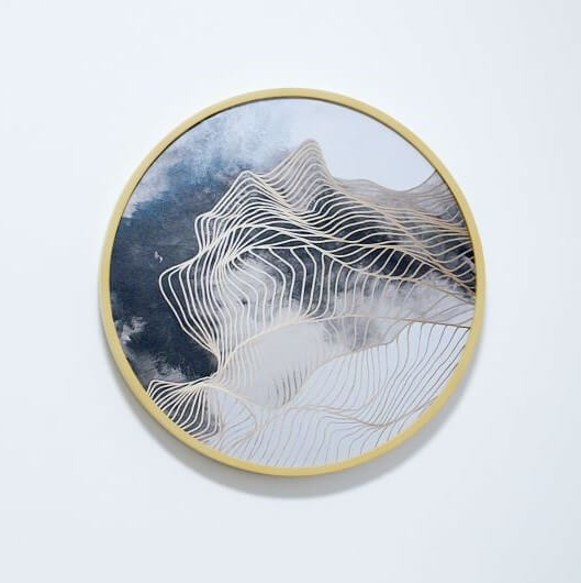 Circle embroidery hoop with wavy gold lines over blue and gray clouds.