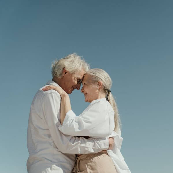 Man and woman clothed in white who are hugging each other and looking in each others eyes