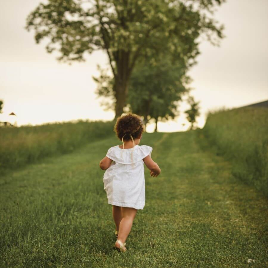 Toddler in white running away from the camera on grass