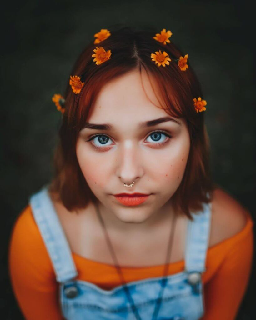 Girl with orange flowers in her hair looking at camera