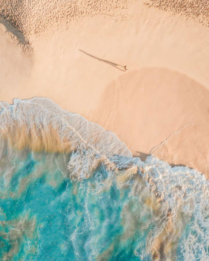 Aerial view of person walking on sand away from sea