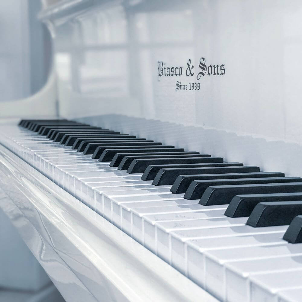 Angled photo of white piano with black and white keys