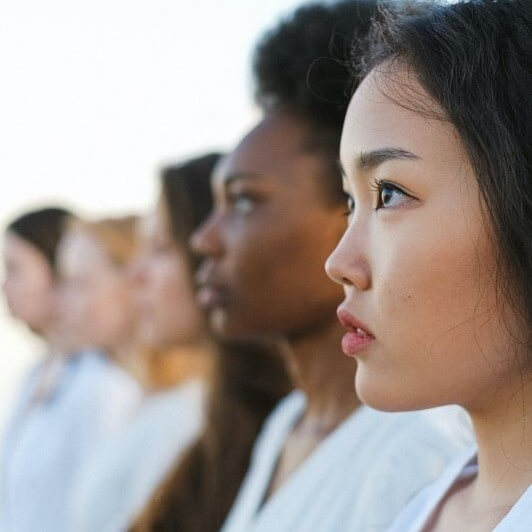 Women dressed in white standing in a row.